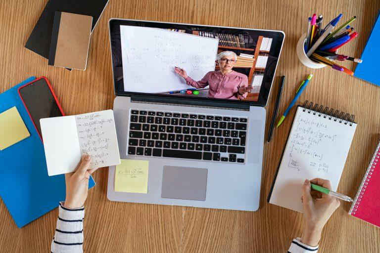 Photo of a laptop showing a teacher teaching